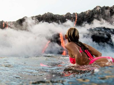 Alison Teal surfing past the Kilauea Volcano