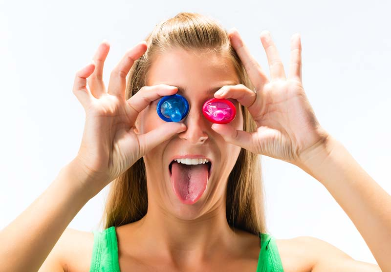A woman holding two rolled condoms over her eyes and sticking her tongue out.