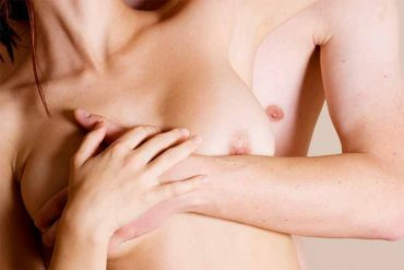 Couple with man holding a woman from behind, showing both of their breasts.