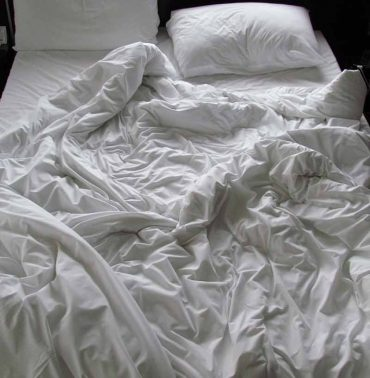 Nice black and white shot of an unmade bed.