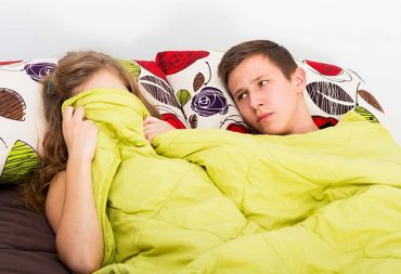 A couple in bed, woman has blanket over her face, with her partner looking at her, not knowing what's going on.
