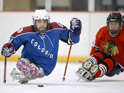 Sled hockey skater going for the puck.