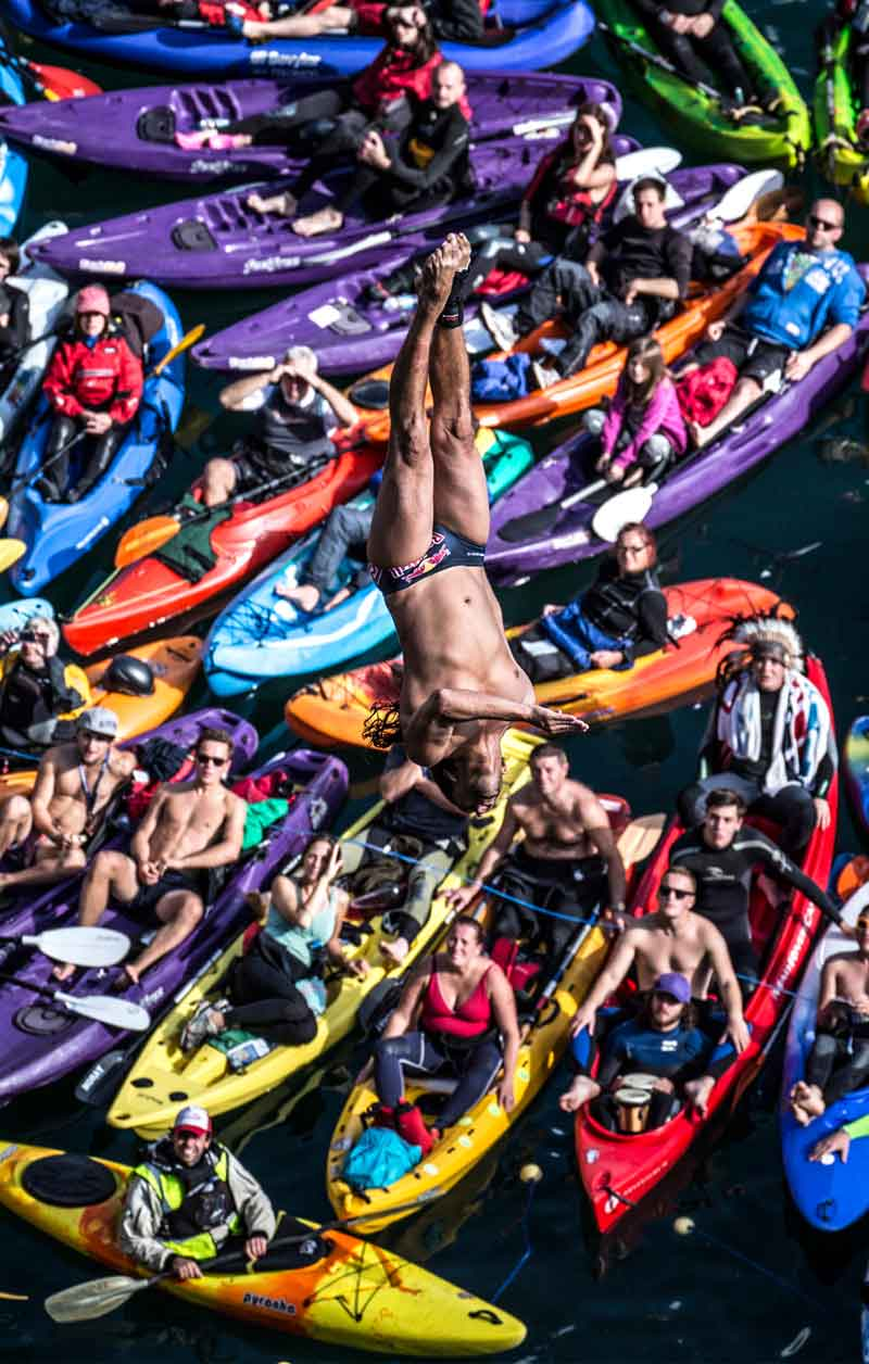 Cliffdiver in a spectacular photo with dozens of colorful boats in the background.