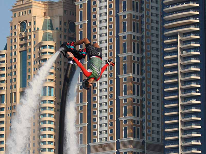 Flyboarding woman doing a flip with tall buildings in the background.