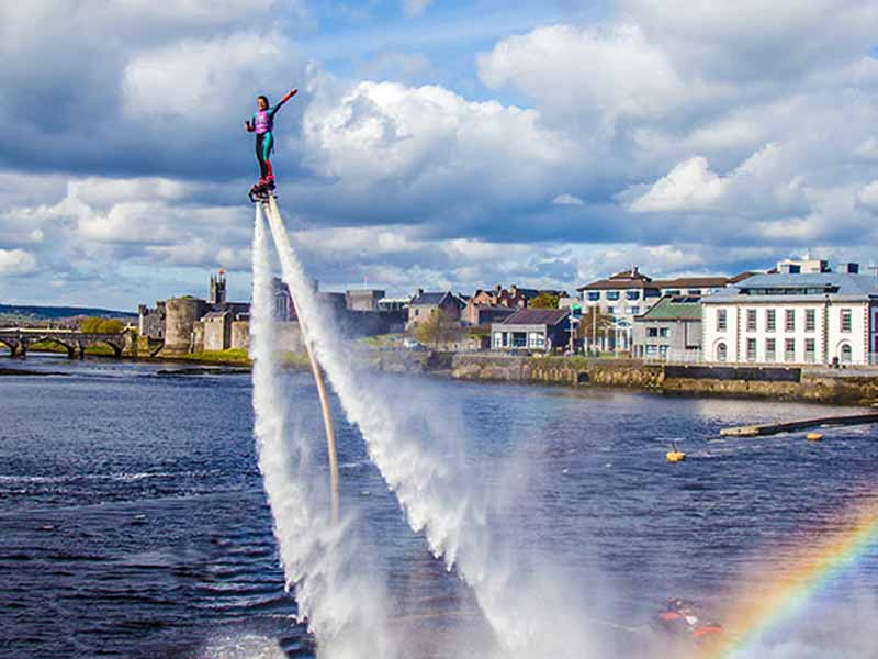 Woman flyboarding high in the sky with a beautiful sky and castle in the background.