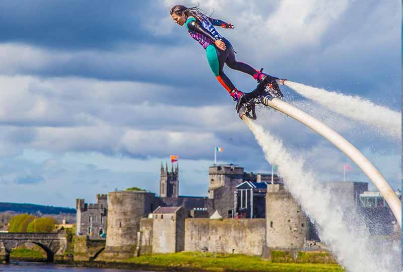Woman skyboarding with a castle in the background.