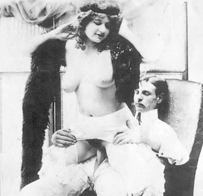A porn image from the 1800s, showing a woman and man having intercourse while he's sitting in a large chair and facing away from him (reverse cowgirl).