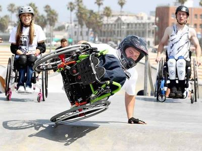 Wheelchair skateboarder handstand.