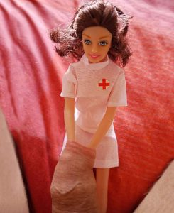 A Barbie like nurse with her plastic arms pulling apart a real human foreskin.