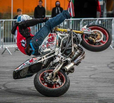 Motorcycle rider doing a radical pivot trick.