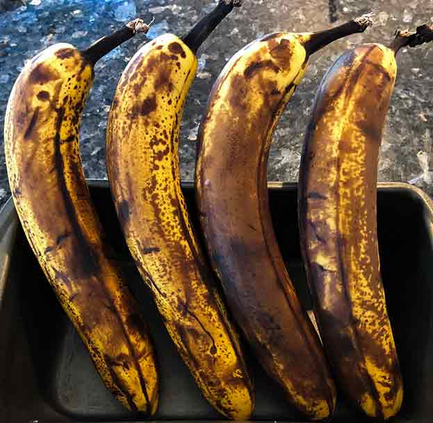 Four extra ripe bananas with a far amount of dark blotching on the peels.