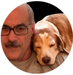 Dr. Paul with Woody the beagle sleeping on his shoulder.