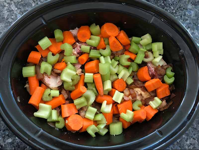 Looking into a slow cooker with raw carrots and celery layered over pieces of rotisserie chicken and sautéed onions.