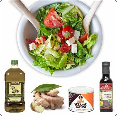 A bowl of fresh salad with these four ingredients below it: Olive Oil, Ginge, Tahini and Balsamic Vinegar.