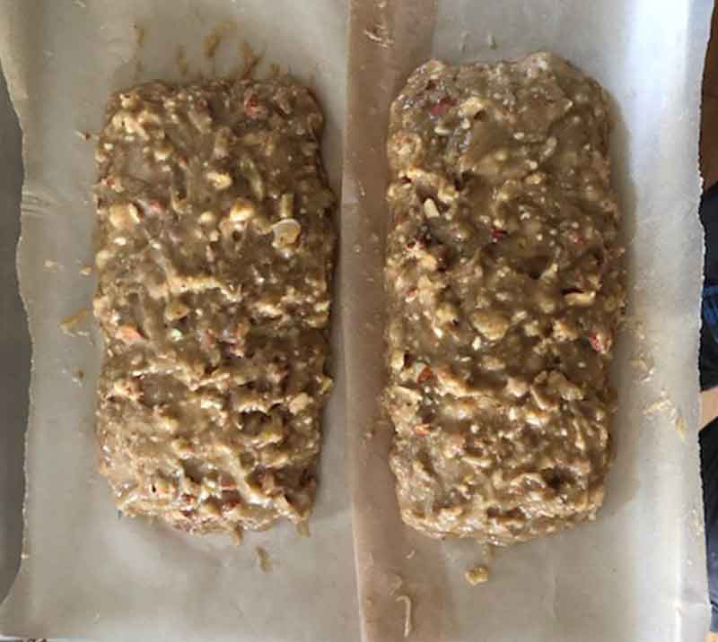 The freshly poured batter in two loaves of biscotti on parchment paper a baking tray before being baked